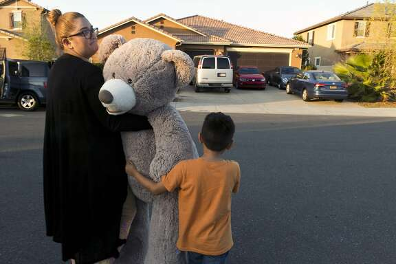 """In this Thursday, Jan. 18, 2018, photo neighbors, Liza Tozier and her son Avery Sanchez, 6, drop off his large """"Teddy"""" as a gift for the children who lived on a home where police arrested a couple on Sunday accused of holding 13 children captive in Perris, Calif. Psychological experts say 13 children rescued from what was described as nothing less than a torture chamber will have years of therapy ahead as they learn to live in a world that, until a week ago, they never really knew existed. Authorities say the children of David and Louise Turpin of Perris, Calif., were confined to the house, chained to furniture and starved. (AP Photo/Damian Dovarganes)"""
