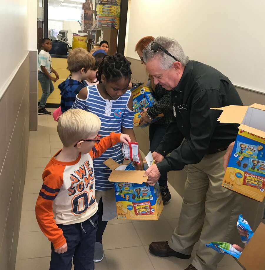 Last Friday Conroe Noon Lion Club volunteers rewarded students at their adopted school of Reaves Elementary with goodies for excellent conduct grades during this 9 week grading period; pictured is Lion Greg Zachary. Photo: Submitted Photo