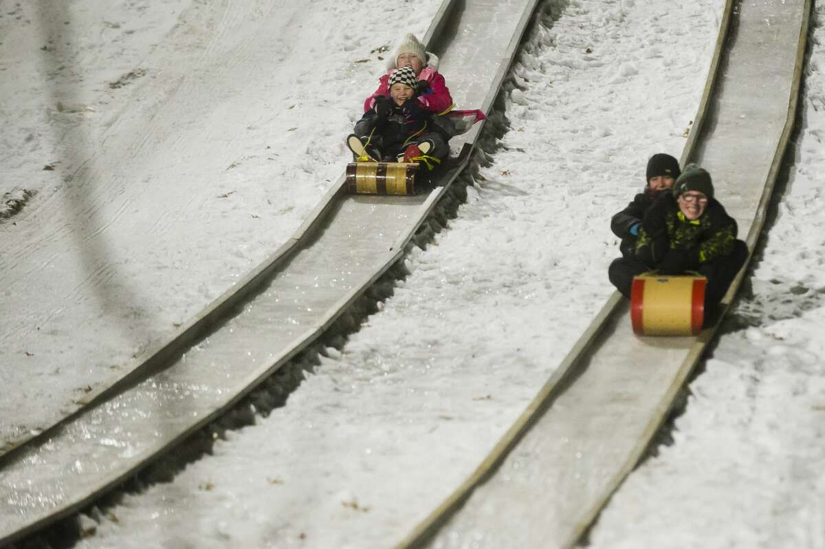 People fly down the toboggan runs during the Snow and Glow event at Midland City Forest on Friday, Jan. 19, 2018. (Katy Kildee/kkildee@mdn.net)