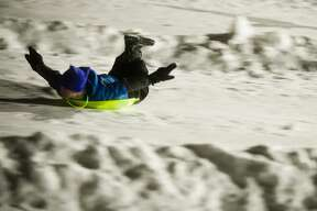 People fly down the sledding hill during the Snow and Glow event at Midland City Forest on Friday, Jan. 19, 2018. (Katy Kildee/kkildee@mdn.net)