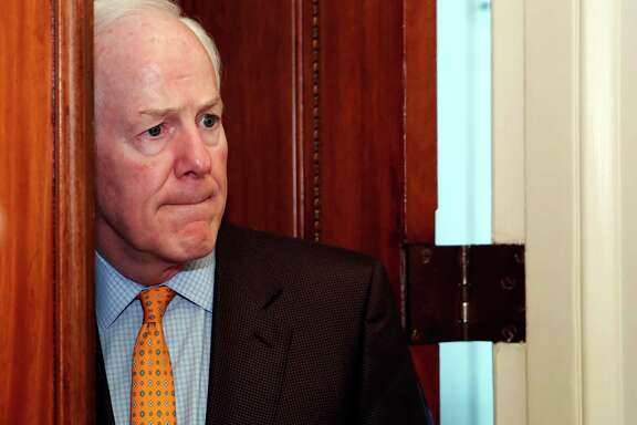 Senate Majority Whip Sen. John Cornyn, R-Texas, pauses to listen to a reporter's question as he enters his office on Capitol Hill, Friday, Jan. 19, 2018 in Washington. (AP Photo/Alex Brandon)