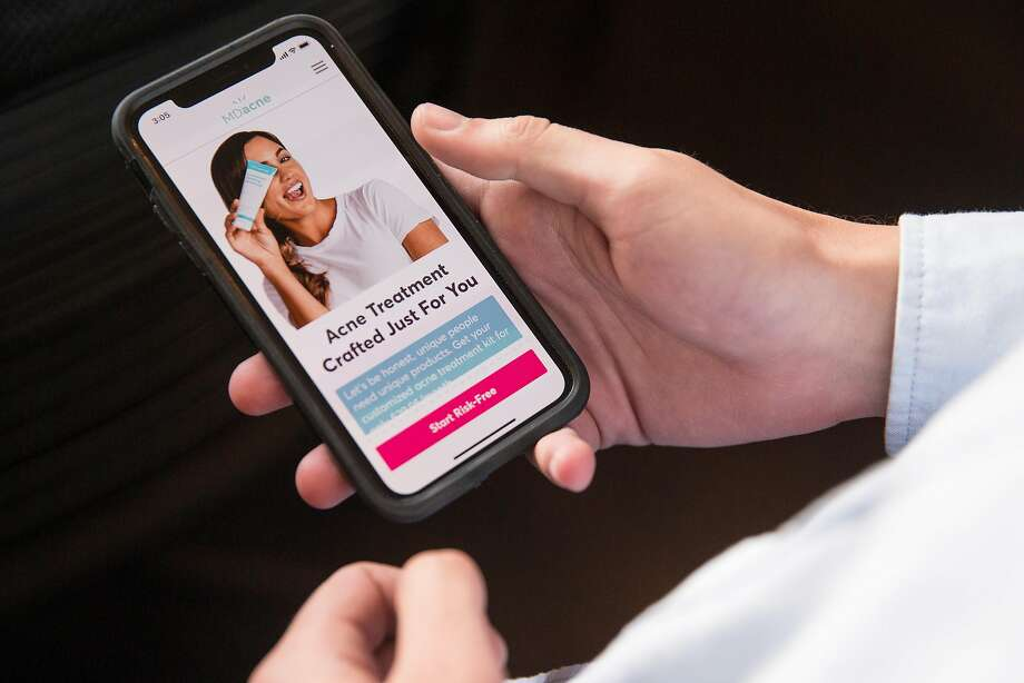 Harth displays the MDacne app, which allows users to take a selfie, send it to the company and get recommendations for treatment. Photo: Jessica Christian, The Chronicle