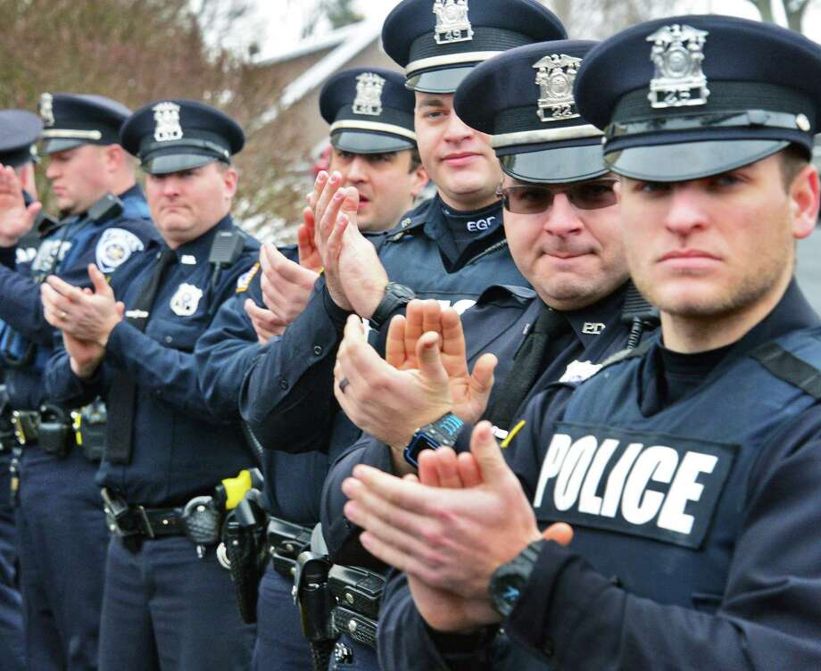 Members of the East Greenbush Police Department applaud Sgt. Rich Edberg, retiring after more than 30 years with the department, during his walking out ceremony Friday Jan. 19, 2018 in East Greenbush, NY.  (John Carl D'Annibale/Times Union) Photo: John Carl D'Annibale / 20042698A