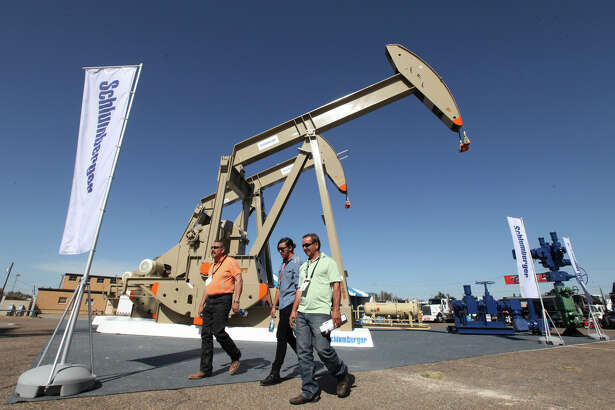 FILE - In this Tuesday, Oct. 18, 2016, file photo, oil show attendees walk past the Schlumberger booth at the Permian Basin International Oil Show at Ector County Coliseum, in Odessa, Texas. Schlumberger N.V. reports financial results Friday, Jan. 19, 2018. (Jacob Ford/Odessa American via AP, File)