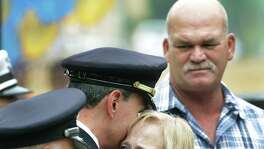 Jane Williams, aunt of Robert Deckard, the San Antonio Police Department officer who died Dec. 20, 2013, is comforted by Police Chief William McManus at a tribute to the department's fallen officers in 2014.