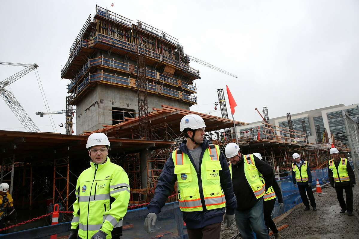 Bob Myers (center) visits the construction site of the Chase Center, Thursday, Jan. 18, 2018, in San Francisco, Calif. The Chase Center will be the new home court of the Golden State Warriors. The center is expected to be completed in 2019.