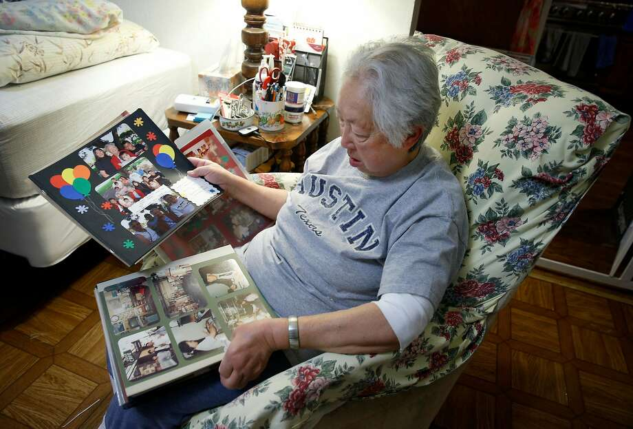 Linda Rosario views pictures of her mother on pages from a family photo album at her home in San Francisco. Her 103-year-old mother, Penny Fong, has lived at the Irene Swindells Alzheimer's residential care facility since 2015. Photo: Paul Chinn, The Chronicle
