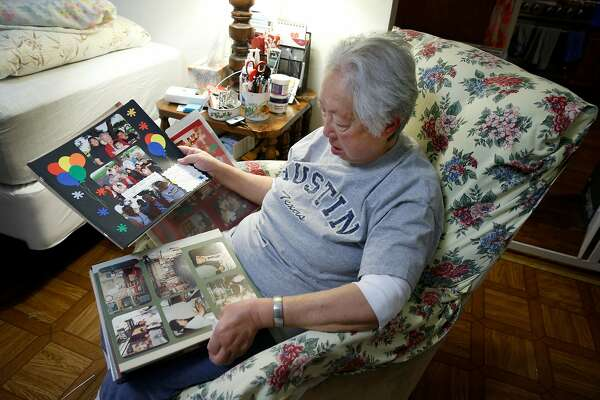 Linda Rosario views pictures of her mother on pages from a family photo album at her home in San Francisco, Calif. on Wednesday, Jan. 17, 2018. Rosario has until November to find a new home for her 103-year-old mother Penny Fong who is one of 19 residents remaining at the Irene Swindells Alzheimers Residential Care Program operated at California Pacific Medical Center. Sutter Health plans to close Swindells when the medical center relocates to Van Ness Avenue.
