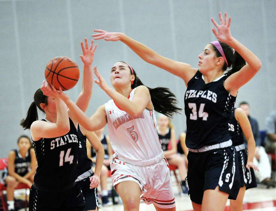 Arianna Gerig of (#34) Staples, right, and teammate, Sophie Smith (#14), left, attempt to stop a driving Kimberly Kockenmeister, center, of Greenwich,  during the girls high school basketball game between Greenwich High School and Staples High School at Greenwich, Conn., Friday, Jan. 19, 2018. Photo: Bob Luckey Jr. / Hearst Connecticut Media / Greenwich Time