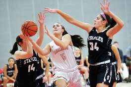 Arianna Gerig of (#34) Staples, right, and teammate, Sophie Smith (#14), left, attempt to stop a driving Kimberly Kockenmeister, center, of Greenwich,  during the girls high school basketball game between Greenwich High School and Staples High School at Greenwich, Conn., Friday, Jan. 19, 2018.