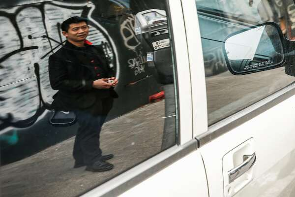 Magician Dan Chan is seen reflected in a parked car Tuesday, Jan. 16, 2018 on Golden Gate Avenue in San Francisco, Calif. near where his car was broken into and his magic back was stolen in August.
