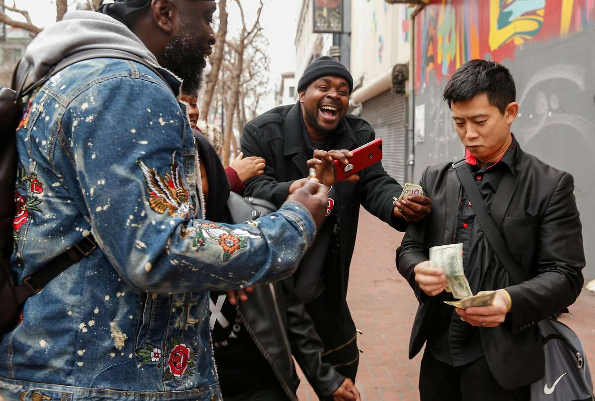 A.J. T., left, and Lee Wilson react after Magician Dan Chan performs a trick for them Tuesday, Jan. 16, 2018 near Market and 6th streets in San Francisco, Calif.