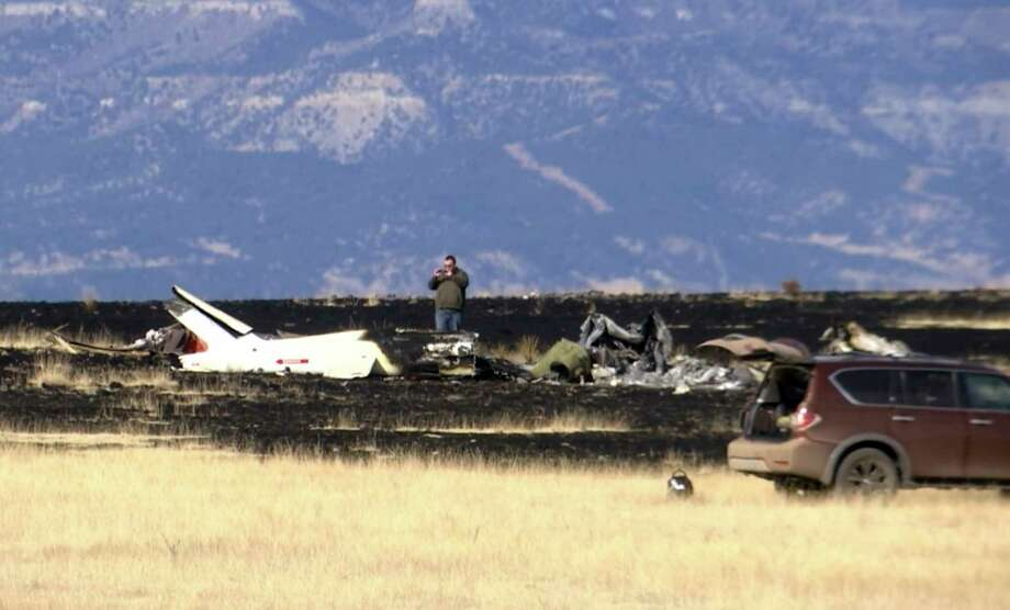 This image taken from video shows an investigator photographing the scene near Raton, N.M., Friday, Jan. 19, 2018, where a helicopter crashed late Wednesday, Jan. 17, 2018. Friends and family members confirmed Thursday, Jan. 18, 2018, that Zimbabwe opposition leader Roy Bennett and his wife, Heather, were on the copter as they traveled to New Mexico to spend their holiday with friend and wealthy businessman Charles Burnett III at his ranch. (AP Photo/Peter Banda) Photo: Peter Banda, STF / Copyright 2018 The Associated Press. All rights reserved.