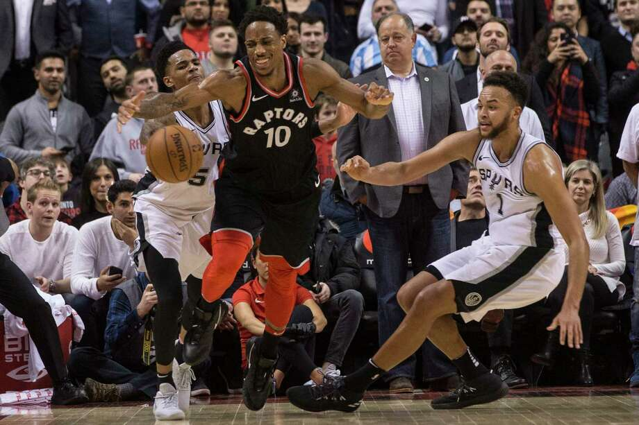 Toronto Raptors guard DeMar DeRozan (10) battles for the the ball with San Antonio Spurs guard Dejounte Murray (5) and forward Kyle Anderson (1) during the second half of an NBA basketball game Friday, Jan. 19, 2018, in Toronto. (Chris Young/The Canadian Press via AP) Photo: Chris Young, Associated Press / The Canadian Press