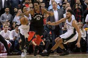 Toronto Raptors guard DeMar DeRozan (10) battles for the the ball with San Antonio Spurs guard Dejounte Murray (5) and forward Kyle Anderson (1) during the second half of an NBA basketball game Friday, Jan. 19, 2018, in Toronto. (Chris Young/The Canadian Press via AP)