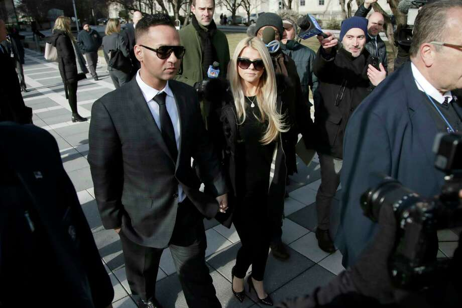 "Michael ""The Situation"" Sorrentino, left, one of the former stars of the ""Jersey Shore"" reality TV show, walks with his fiancee Lauren Pesce while leaving the Martin Luther King, Jr., Federal Courthouse after a hearing, Friday, Jan. 19, 2018, in Newark, N.J. Sorrentino pleaded guilty to one count of tax evasion and admitted concealing his income in 2011 by making cash deposits in amounts that wouldn't trigger federal reporting requirements. He and his brother, Marc, were charged in 2014 and again last year with multiple counts related to nearly $9 million in income from the show. (AP Photo/Julio Cortez) Photo: Julio Cortez / Copyright 2018 The Associated Press. All rights reserved."