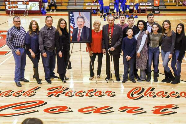 Former Martin player and head coach Hector Chacon poses for a photo with his family Friday during a dedication ceremony naming the court after him before the Tigers' 82-27 victory.