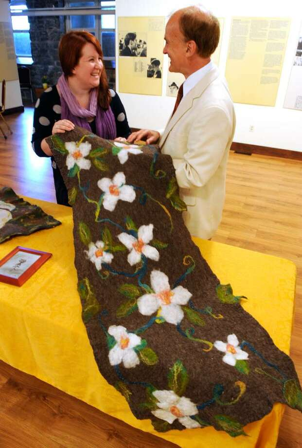 "Mechanicville School art teacher Kate Dollard and Jaimen McMillan, director of the Arts Center on the Hudson, hold one of the many pieces of art for ""The White Rose"" exhibit. (Skip Dickstein / Times Union) Photo: Skip Dickstein / 2008"