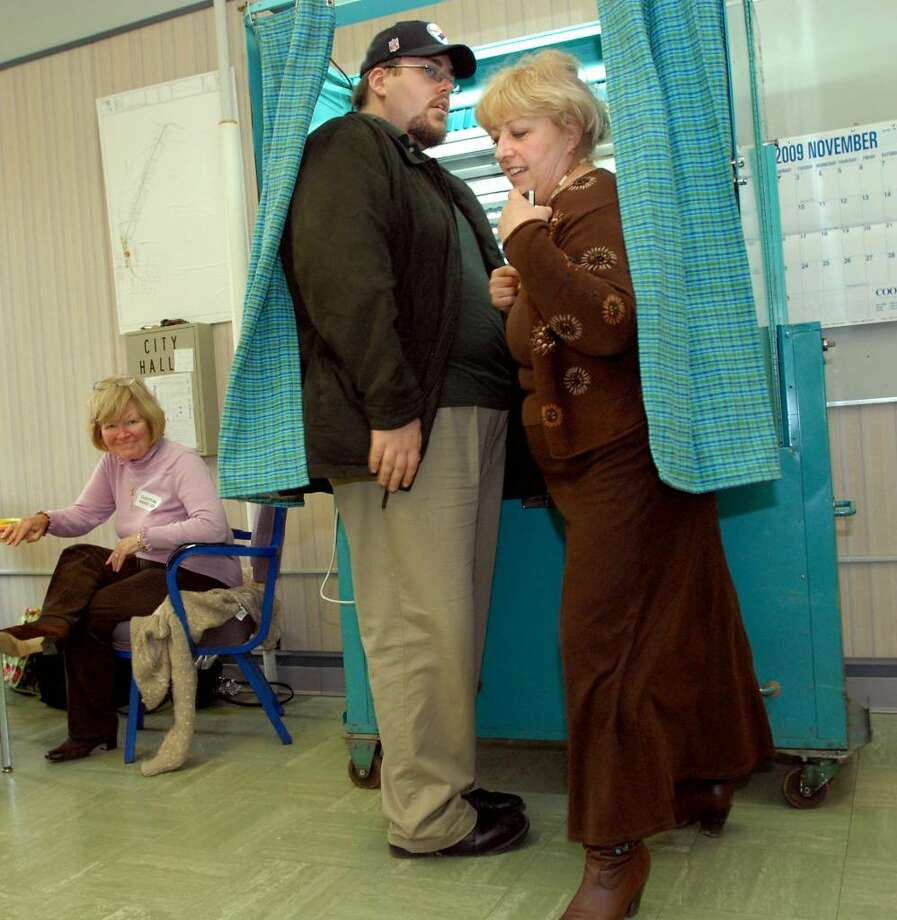 Byron Fonda, center, and his mother, Gloria Fonda, right, who's running for City Council president, exit the voting booth on Tuesday, Nov. 3, 2009, in Rensselaer. (Cindy Schultz / Times Union) Photo: CINDY SCHULTZ
