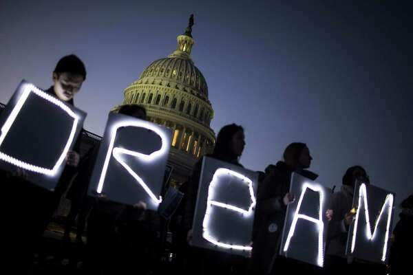Demonstrators hold illuminated signs during a rally supporting the Deferred Action for Childhood Arrivals program outside the U.S. Capitol building in Washington on Jan. 18, 2018. MUST CREDIT: Bloomberg photo by Zach Gibson.