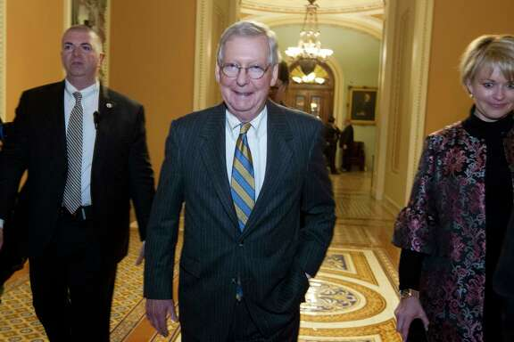 Senate Majority Leader Mitch McConnell, center, R-Ky., walks to his office early Saturday, Jan. 20, 2018, at the Capitol in Washington. The federal government shut down at the stroke of midnight Friday, halting all but the most essential operations.