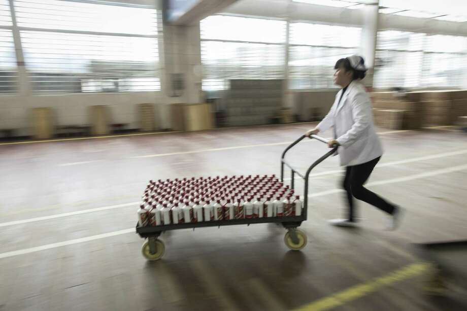 An employee moves bottles of Moutai baijiu at the Kweichow Moutai factory in the town of Maotai in Renhuai, Guizhou province, China, on Dec. 14, 2017. ( Photo: Qilai Shen/Bloomberg) / Bloomberg