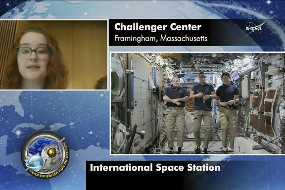 In this image made from video provided by NASA, astronauts Scott Tingle, Joe Acaba, Norishige Kanai, aboard the International Space Station, take questions from students at Framingham State University in Framingham, Mass., on Friday, Jan. 19, 2018. Thirty-two years after the Challenger disaster, teachers turned astronauts Acaba and Ricky Arnold will pay tribute to Christa McAuliffe by carrying out her science classes on the International Space Station. (NASA via AP)