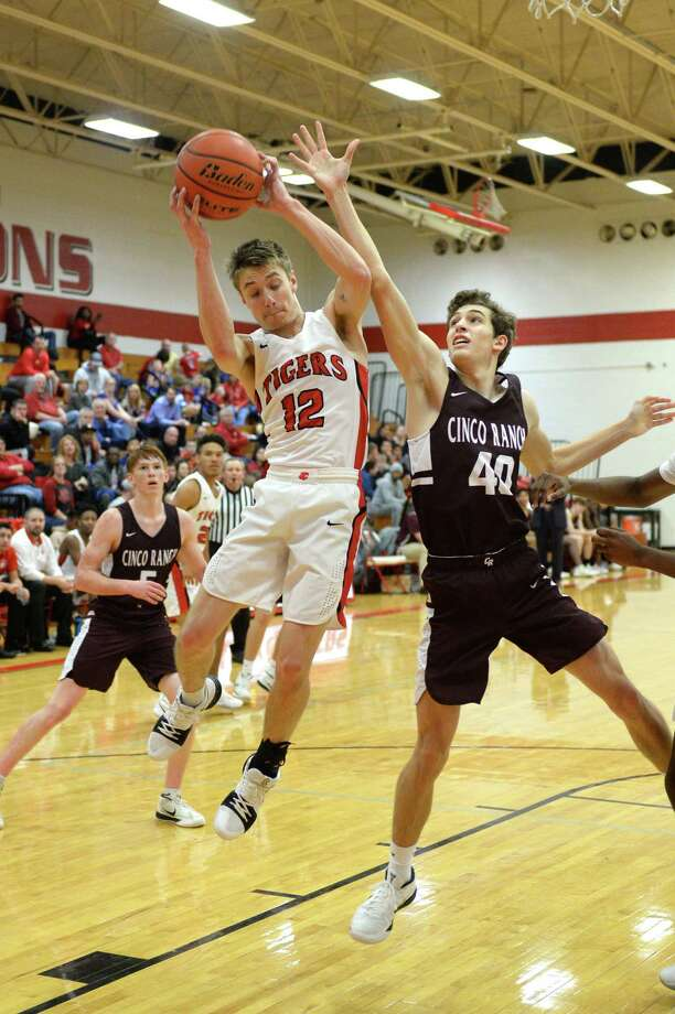 Dane Geddes (12) of Katy and Jackson Cobb (40) of Cinco Ranch compete for a rebound during the first half of a varsity boys basketball game between Katy Tigers and the Cinco Ranch Cougars on Friday January 19, 2018 at Katy HS, Katy, TX. Photo: Craig Moseley, Staff / ©2018 Houston Chronicle