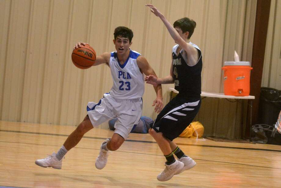 Plainview Christian Academy's Kaleb Naceanceno, left, drives to the basket during a game earlier this season. The senior guard scored 25 points in PCA's district opener Friday night Photo: Skip Leon/Plainview Herald