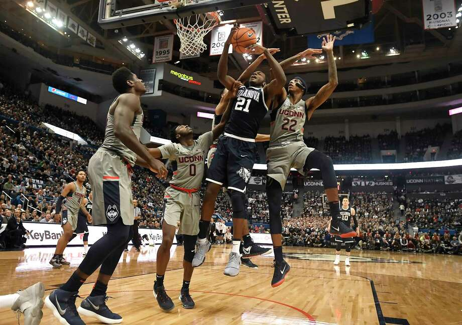 Villanova's Dhamir Cosby-Roundtree (21) is fouled from behind by Connecticut's Tyler Polley as Connecticut's Antwoine Anderson (0) and Terry Larrier (22) defend during the first half of an NCAA college basketball game, Saturday, Jan. 20, 2018, in Hartford, Conn. Photo: Jessica Hill, AP / AP2018