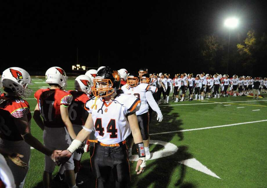 The Ridgefield High School football team, right,  shakes hands with the Greenwich High School football at the end of the game under the lights at Cardinal Stadium in Greenwich, Conn., Saturday, Nov. 4, 2017. Greenwich remained undefeated winning the game 26-21 over Ridgefield. Photo: Bob Luckey Jr. / Hearst Connecticut Media / Greenwich Time