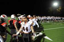 The Ridgefield High School football team, right,  shakes hands with the Greenwich High School football at the end of the game under the lights at Cardinal Stadium in Greenwich, Conn., Saturday, Nov. 4, 2017. Greenwich remained undefeated winning the game 26-21 over Ridgefield.