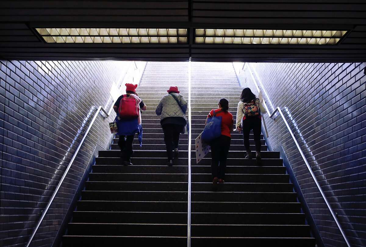 Four women make their way up the stairs from the Civic Center Bart Station to the Women�s March at Civic Center Plaza Saturday, Jan. 20., 2018 in San Francisco, Calif.