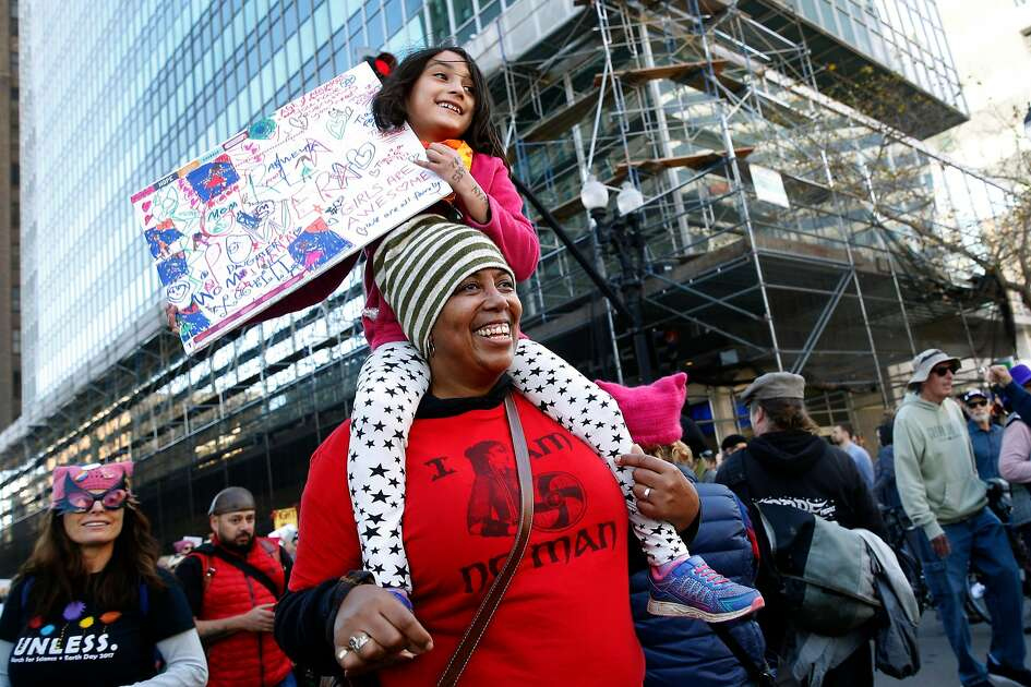 Patrina Williams carries goddaughter Xochitl Catanzano-Rios, 6, on her shoulders at 14th Street and Broadway as thousands participate in the Women's March and rally in Oakland, Calif. on Saturday, Jan. 20, 2018.