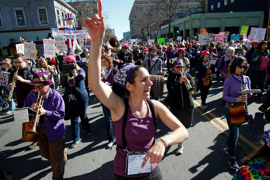 Musical director Sarah Rosenkrantz leads the Nasty Woman Band down 14th Street as thousands participate in the Women's March and rally in Oakland, Calif. on Saturday, Jan. 20, 2018.