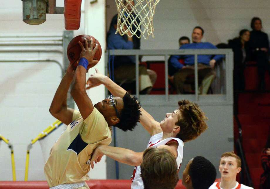 Notre Dame of Fairfield's Noreaga Davis attempts a shot as Fairfield Prep's Jacob McCarthy, at right, defends during Fairfield Prep Holiday Classic basketball action in Fairfield, Conn., on Thursday Dec. 28, 2017. Photo: Christian Abraham / Hearst Connecticut Media / http://connpost.com/