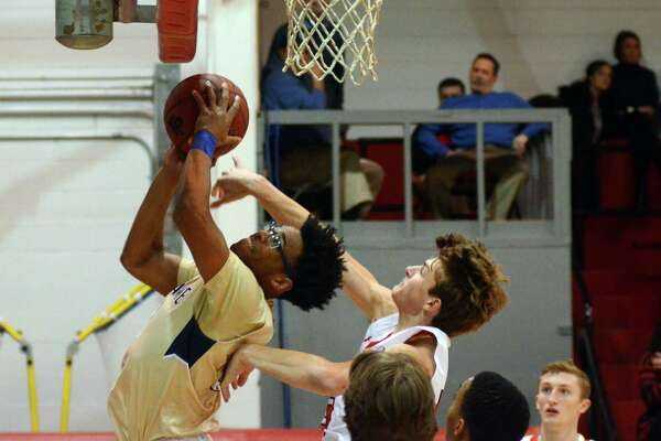 Notre Dame of Fairfield's Noreaga Davis attempts a shot as Fairfield Prep's Jacob McCarthy, at right, defends during Fairfield Prep Holiday Classic basketball action in Fairfield, Conn., on Thursday Dec. 28, 2017.