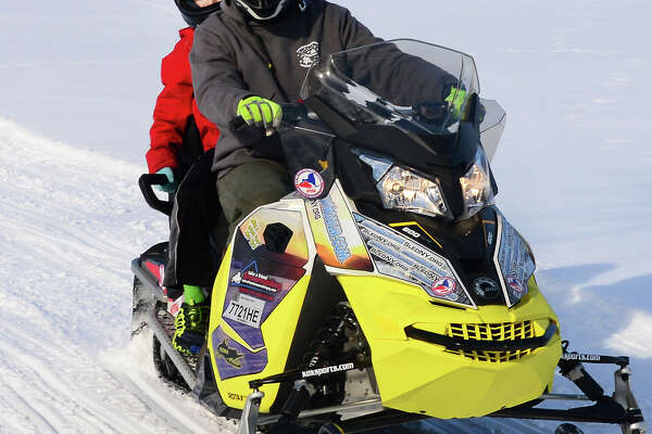 Ten-year-old William Kelly, left, of Greenwich gets a ride along on a NY Snowmobiling Association training sled behind Lincoln Mountain snowmobile club VP Daniel Leerkes during the Take a Friend Snowmobiling event at Hudson Crossing Park Saturday Jan. 20, 2018 in Schuylerville, NY.  (John Carl D'Annibale/Times Union)