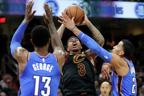 Cleveland Cavaliers' Isaiah Thomas (3) shoots between Oklahoma City Thunder's Paul George (13) and Andre Roberson (21) in the first half of an NBA basketball game, Saturday, Jan. 20, 2018, in Cleveland.