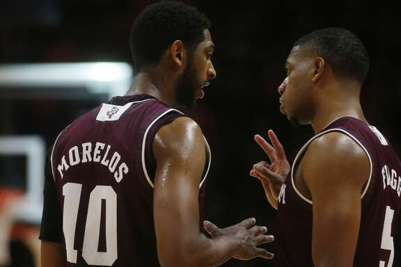 Texas A&M guard Savion Flagg (5) and Texas A&M center Tonny Trocha-Morelos (10) talk during a timeout in the second half of an NCAA college basketball game against Tennessee on Saturday, Jan. 13, 2018, in Knoxville, Tenn. (AP Photo/Crystal LoGiudice)