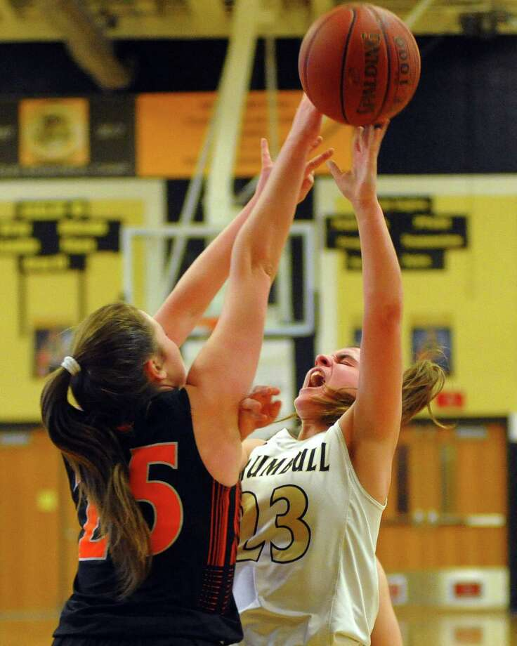 Ridgefield's Norah McNeece (25) attempts to block a shot by Trumbull's Julie Keckler druing theri FCIAC game Saturday in Trumbull. The Tigers won their seventh straight and handed the Eagles their first loss of the season. Photo: Christian Abraham / Hearst Connecticut Media / Connecticut Post