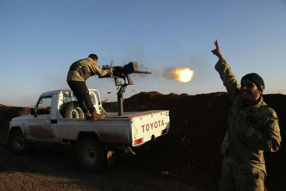 Turkish-backed fighters from the Free Syrian Army fire towards Kurdish People's Protection Units (YPG) positions in the area of Afrin on Saturday.