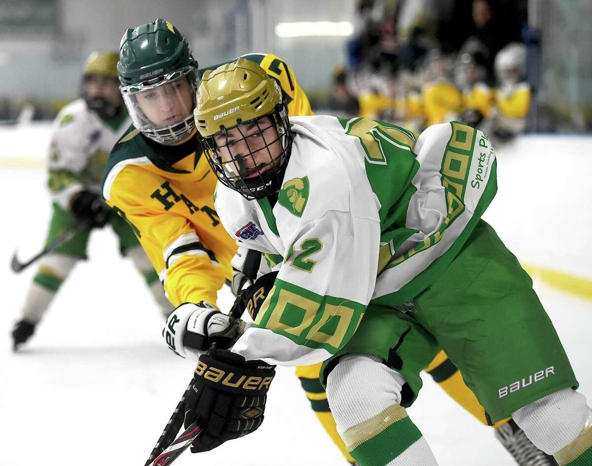 Notre Dame-West Haven freshman forward battles Hamden junior defenseman for a loose puck, Saturday, Jan. 20, 2018, at Astorino Rink in Hamden. Notre Dame won, 5-1.