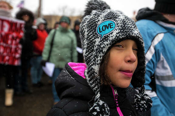 Jamie Bruce, 8, stands with other protesters before a Women's March on Saturday, Jan. 20, 2018, in Casper, Wyo. On the anniversary of President Donald Trump's inauguration, people participating in rallies and marches in the U.S. and around the world Saturday denounced his views on immigration, abortion, LGBT rights, women's rights and more. (Josh Galemore/The Casper Star-Tribune via AP)