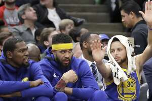 Golden State Warriors' Kevin Durant, left, JaVale McGee, center, and Stephen Curry sit on the bench during the second half of an NBA basketball game against the Chicago Bulls Wednesday, Jan. 17, 2018, in Chicago. The Warriors won 119-112. (AP Photo/Charles Rex Arbogast)