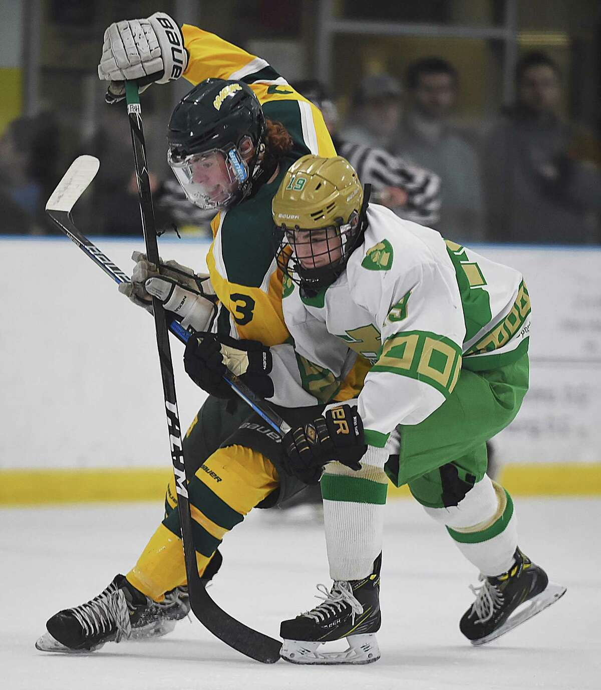 Notre Dame-West Haven defenseman Connor Morgan, right, battles Hamden forward Zach Owens for a loose puck Saturday at Astorino Rink in Hamden.