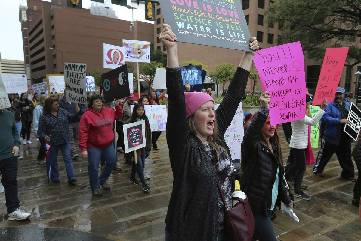 """Ginger Diercks (center) yells, """"This is what democracy looks like,"""" as she and Jane Herzig (right) join about 500 people according to organizers gathered at Main Plaza to take part in the second annual Women's Rally on Saturday, Jan. 20, 2018. The message of the event hosted by TX23 Indivisible, was clear and decisive as speaker after speaker implored those in attendance that women's voices were not be silenced and to vote in upcoming elections. """"When women vote, we win,"""" said Cassandra Littlejohn, Bexar County Democratic Party Political Director. Toward the end of the two-hour rally, a brief march around Main Plaza came together as the event concluded. (Kin Man Hui/San Antonio Express-News)"""