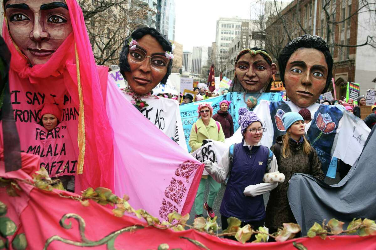 Women walk between giant puppets of notable women made by local artists as thousands march through the streets of Seattle, from Cal Anderson Park to the Seattle Center, for the Women's March 2.0, Saturday, Jan. 20, 2018. Demonstrators came out in support of women's right and immigrant rights and against President Trump's administration.