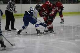 Fairfield Prep's Skyler Celotto and Darien's CJ Hathaway battle for a faceoff during a boys hockey game at Darien Ice Rink in Darien, Conn. Fairfield Prep won 4-1.