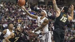 Texas A&M's Duane Wilson (left) shoots in the first half as Missouri's Jordan Geist defends Saturday.